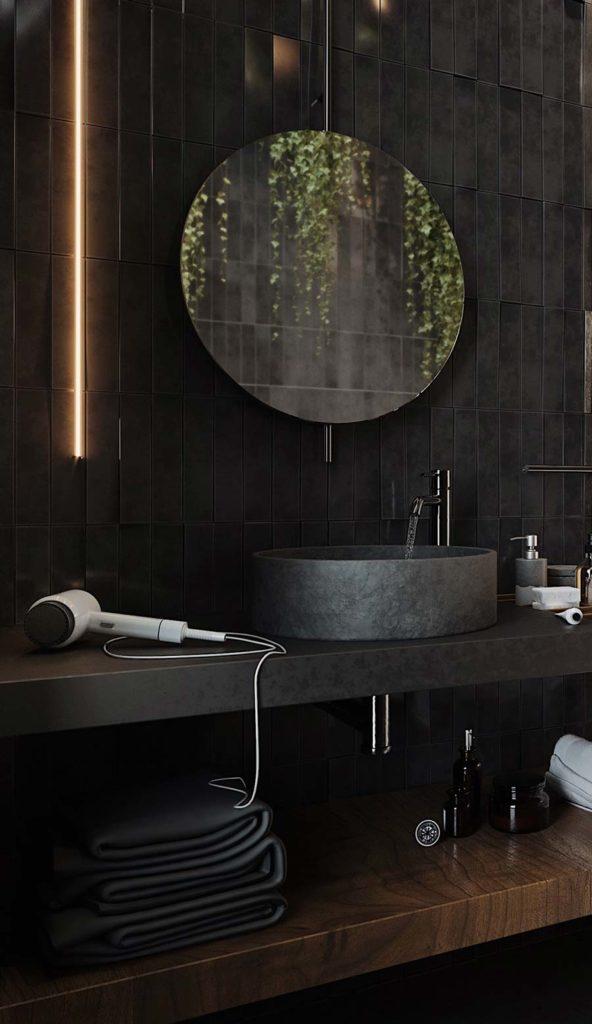 Salle de bain look total black avec une étagère en bois sombre, un miroir rond et un néon lumineux