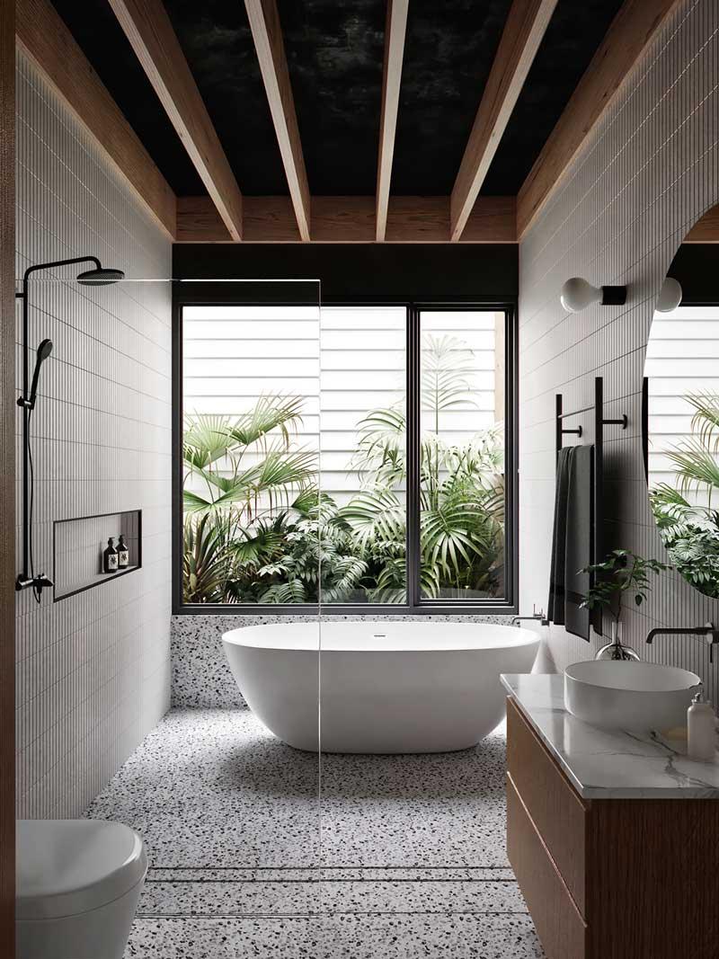 Une salle de bain lumineuse avec du carrelage mural blanc, un sol en terrazzo, et une grande fenêtre qui donne sur le jardin