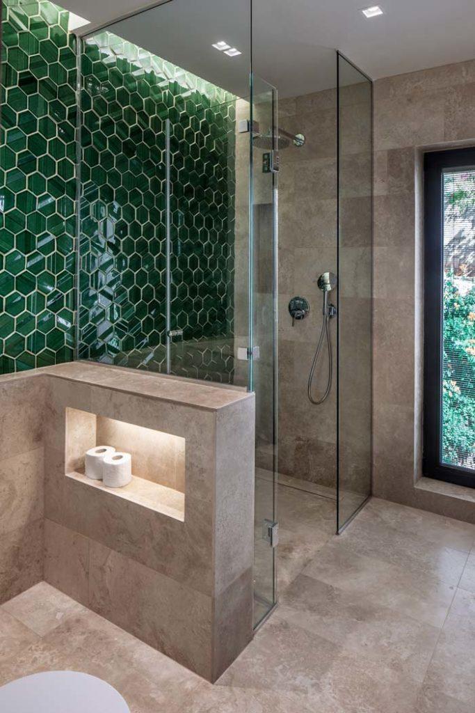 Une salle de bain grise moderne avec une grande cabine de douche transparente et un mur en zellige hexagonal vert émeraude