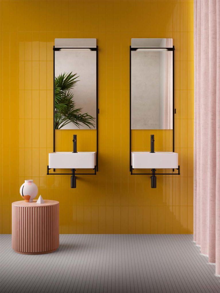 Salle de bain avec un mur en zellige jaune vif, un sol en carrelage blanc, de la petite déco rose et deux grands miroirs rectangulaires avec double vasques