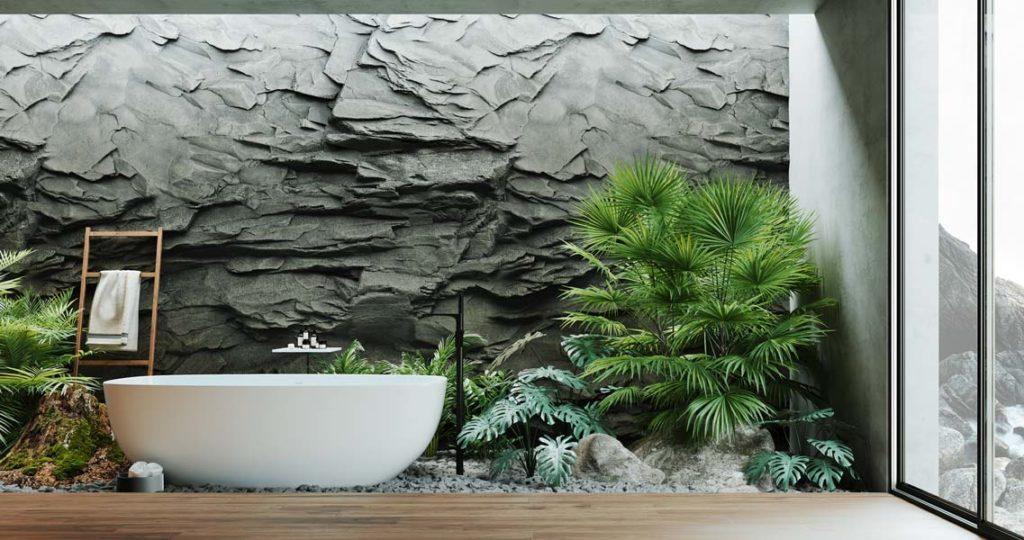 Une salle de bain zen et lumineuse avec un mur en pierre grise, un plancher en bois noble, une baignoire blanche, de la végétation et de la petite déco en bambou