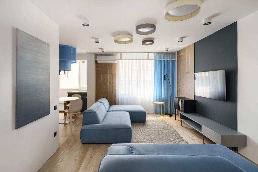 Canapé modulable bleu ciel dans un salon aux revêtements en bois