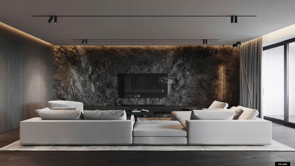Un grand salon chaleureux avec des murs en pierre et bois et un grand canapé blanc au centre