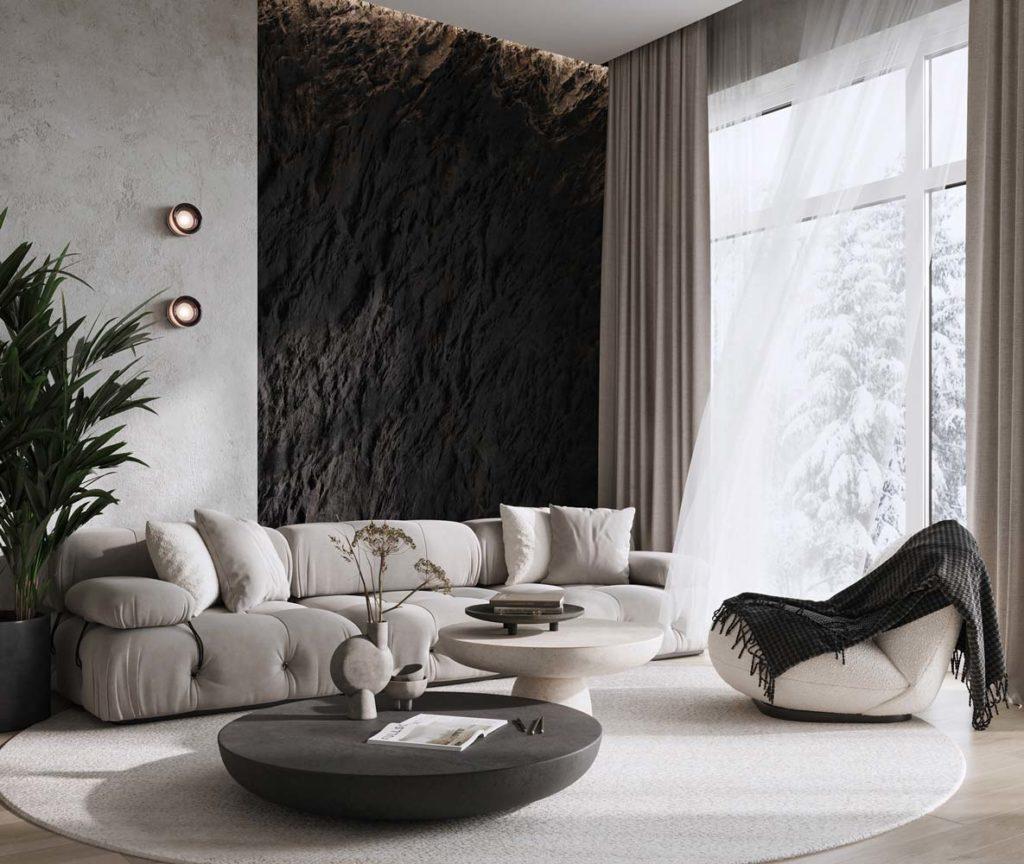 Un coin salon sobre avec un pan de mur en pierre sombre et des meubles ronds et douillets