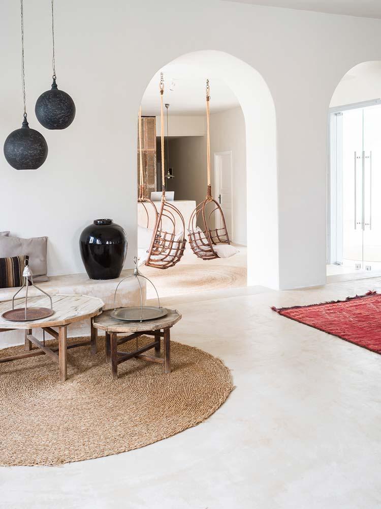 Un salon blanc avec un tapis rond et deux fauteuils suspendus en bois