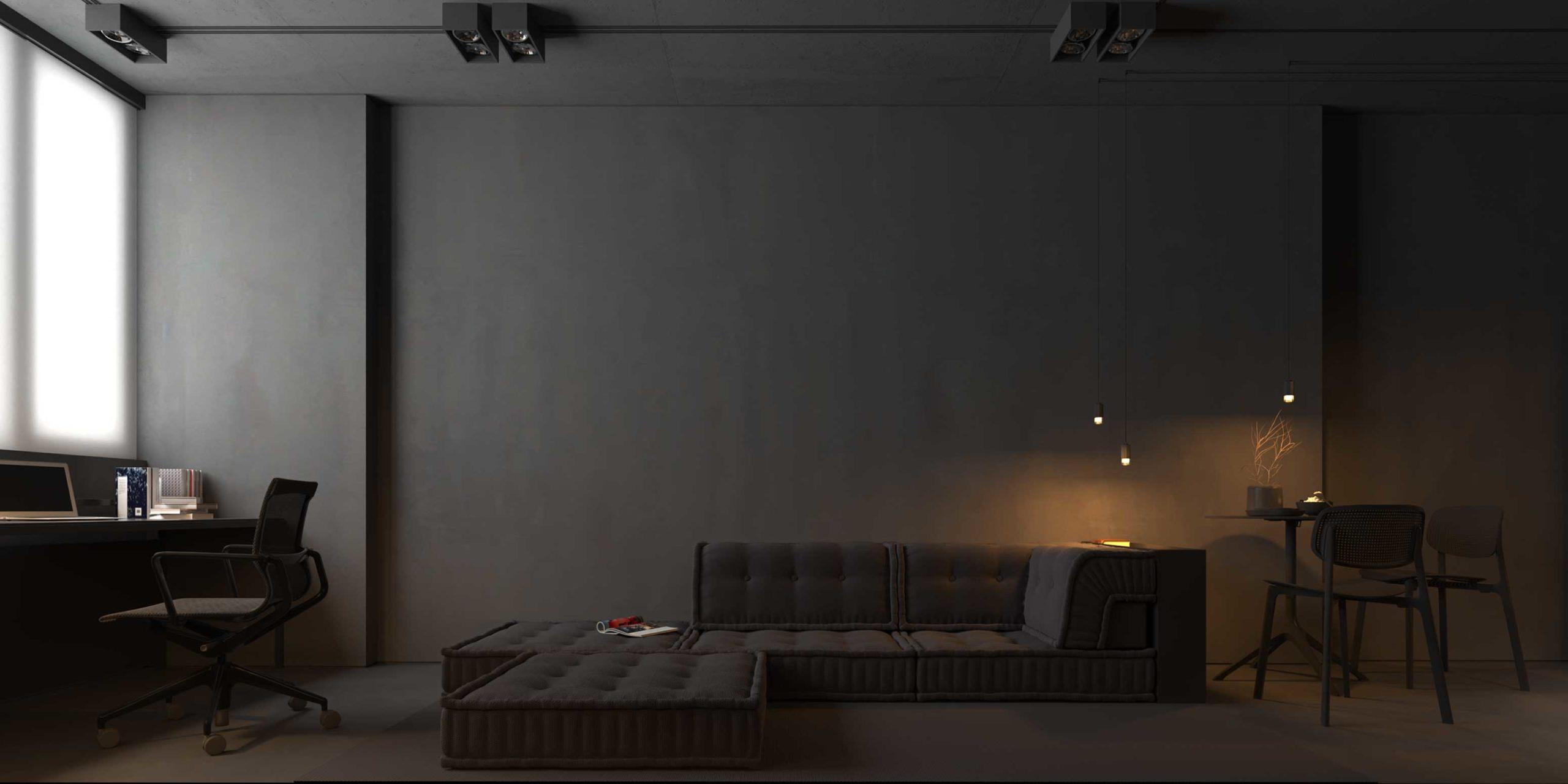 Un canapé modulable noir matelassé dans un salon bureau sombre à l'ambiance feutrée