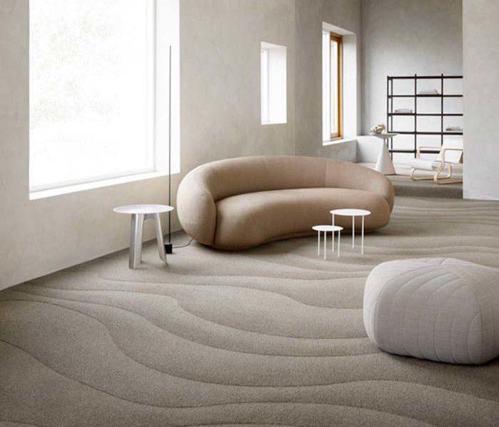Un salon dans le style bord de mer avec du mobilier arrondi et de la moquette imitant les rides de sable des estrans