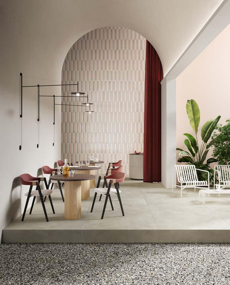 Un salon lumineux avec des plantes vertes, un rideau brun et un pan de mur en zellige rectangulaire blanc et beige