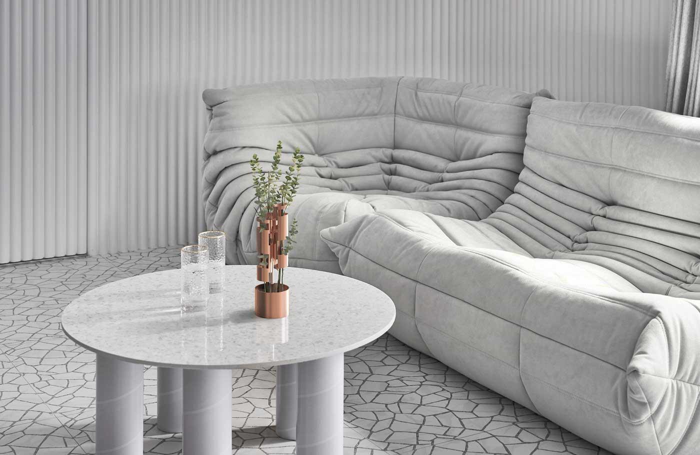 Une table basse avec des pieds en tube et de la petite déco rose gold dans un salon total white