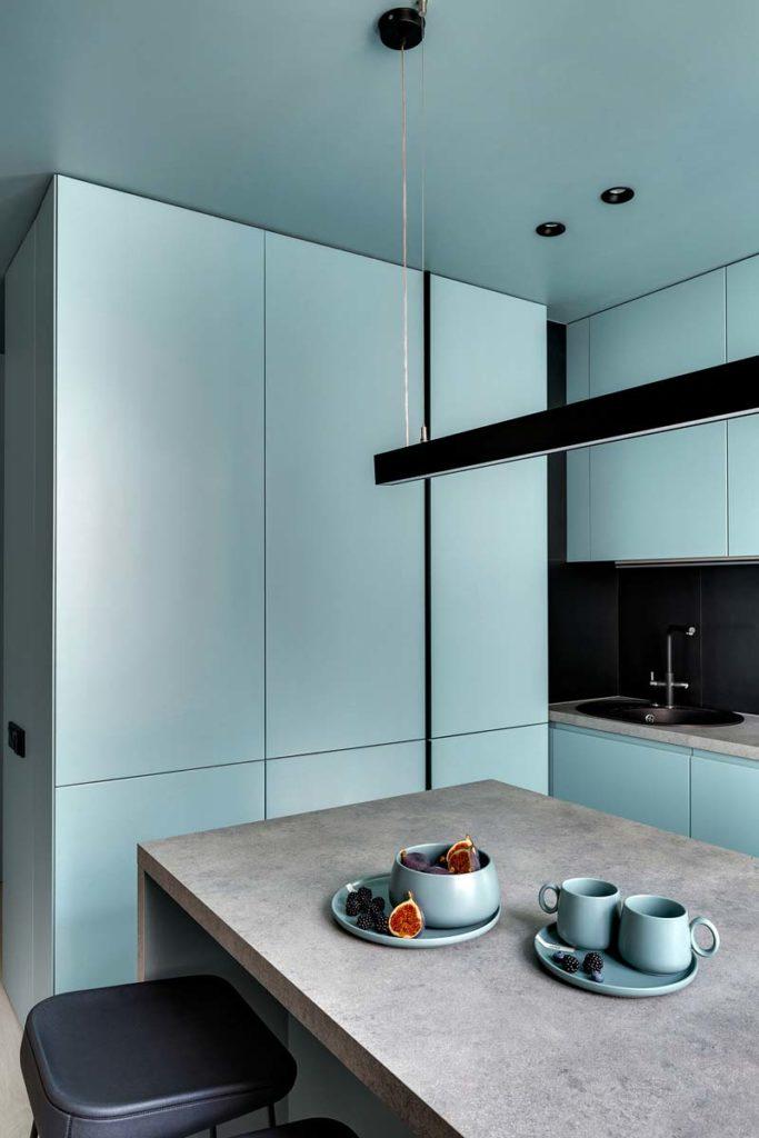 Cuisine aux meubles blue sky avec une table grise et des sièges en cuir