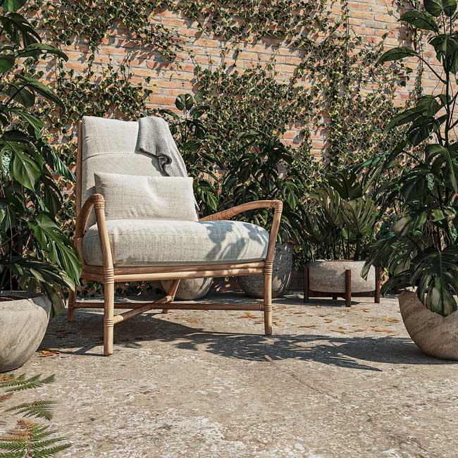 Un fauteuil lounge dans un jardin à l'ambiance méditerranéenne avec un mur en briques et des plantes grimpantes