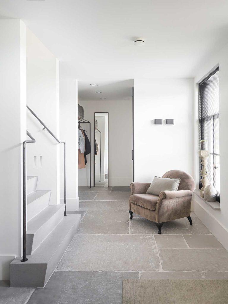 Un intérieur moderne blanc et gris avec des escaliers en béton, un sol en travertin et un fauteuil en velours