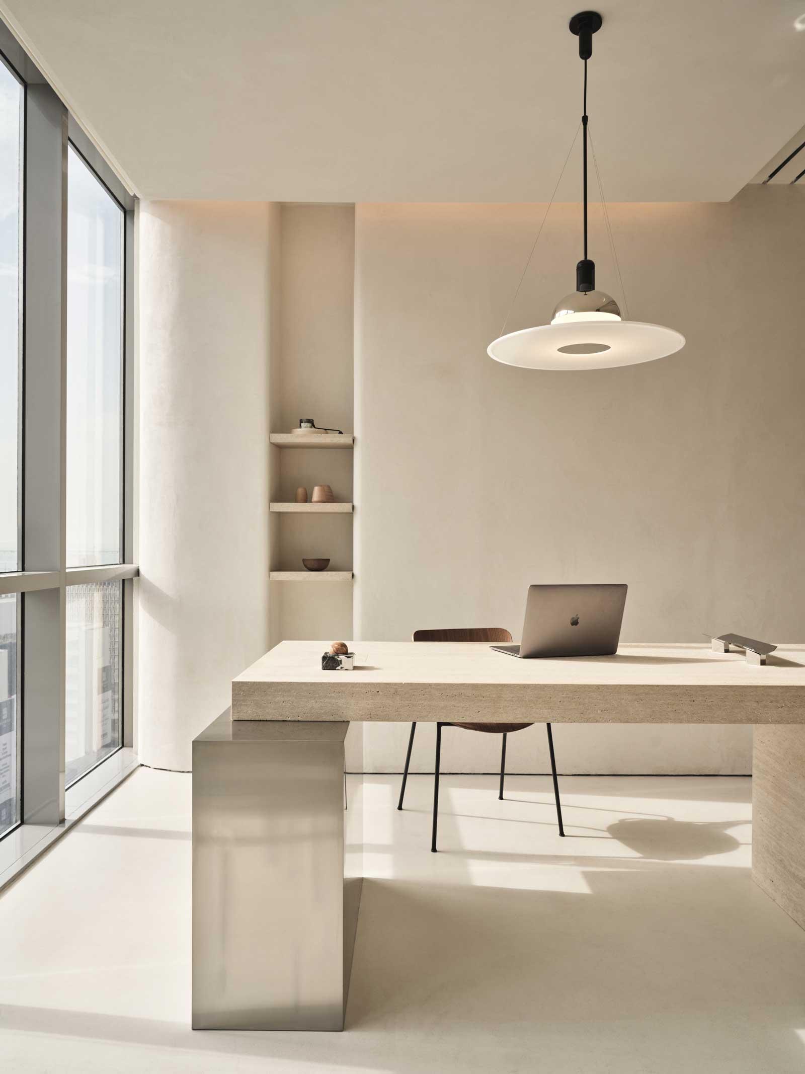 Un bureau lumineux en tadelakt avec de grandes fenêtres et des étagères de rangement
