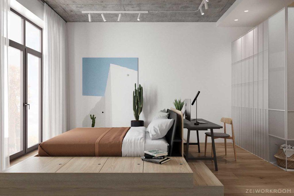 Une estrade en bois blond dans une chambre pour surélever le lit