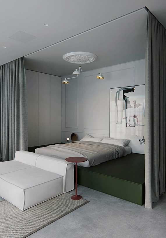 Un lit trône sur une estrade vert kaki entourée de rideaux, qui donne sur le salon