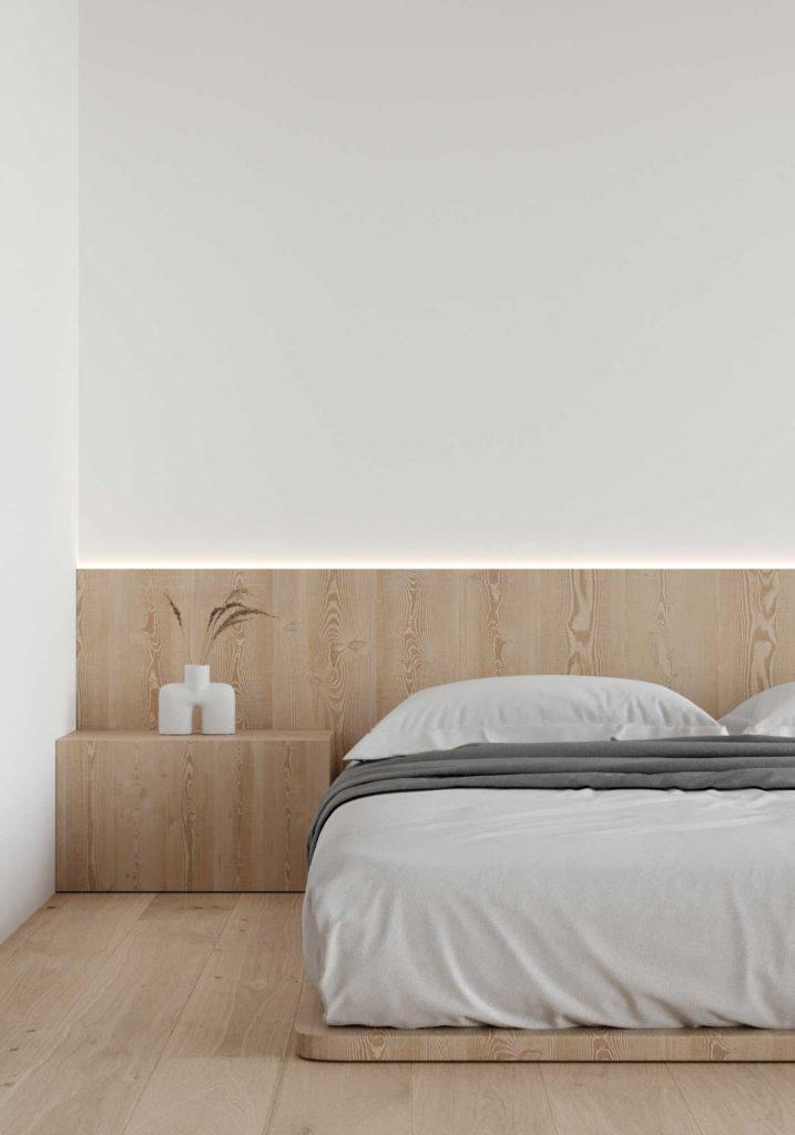 Le bois blond fait office de tête de lit, de table de nuit et surélève légèrement le matelas dans cette chambre minimaliste