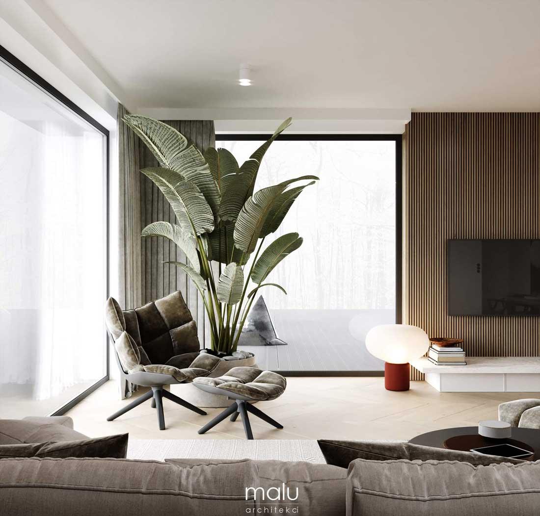 Un arbre intérieur avec de grandes feuilles vertes au coin d'un salon contemporain