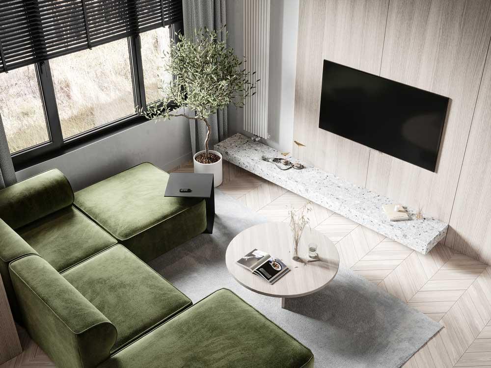 La couleur vert kaki d'un canapé s'accorde avec les feuilles d'un arbre d'intérieur
