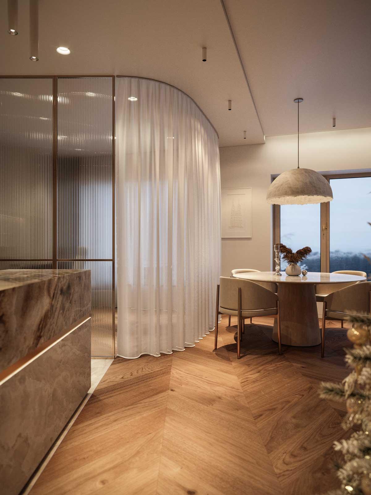 En soirée, des couleurs chaudes pour une atmosphère douce dans cette salle à manger en bois et marbre avec un rideau