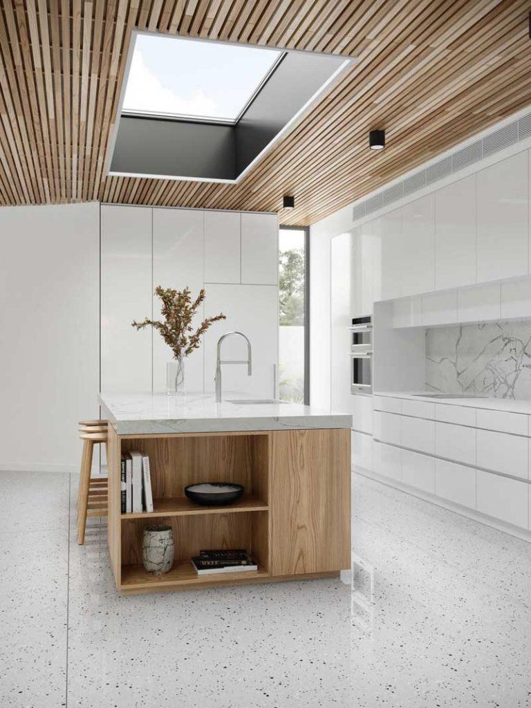 Une cuisine blanche lumineuse avec une crédence en marbre, un îlot central et du bois blond en bardage intérieur au plafond