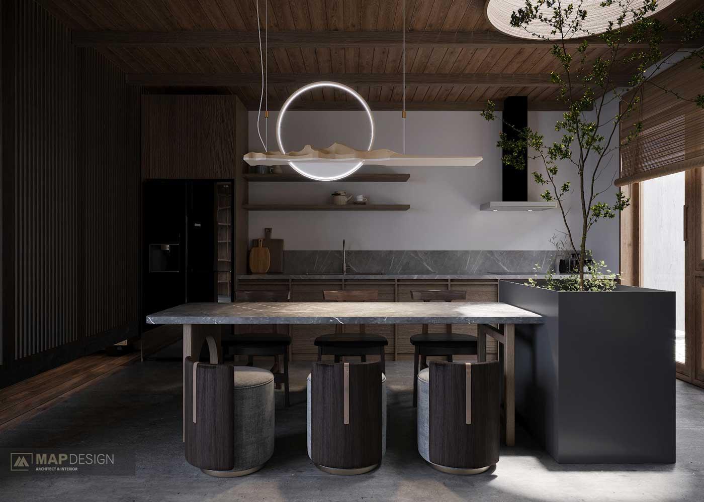 La fragilité des branches fines d'un arbre d'intérieur contraste avec une cuisine sombre en matériaux bruts