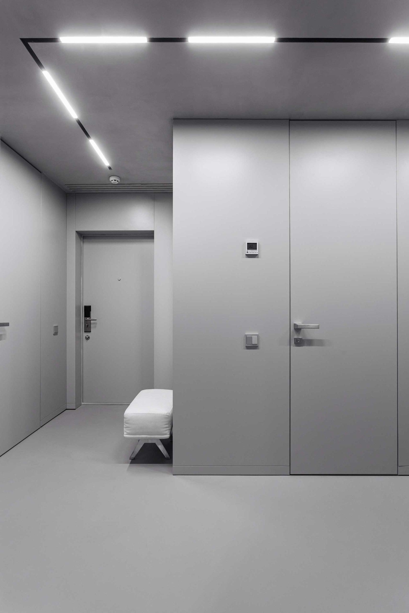 Une entrée minimaliste dans les tons de gris avec éclairages néons et banquette blanche