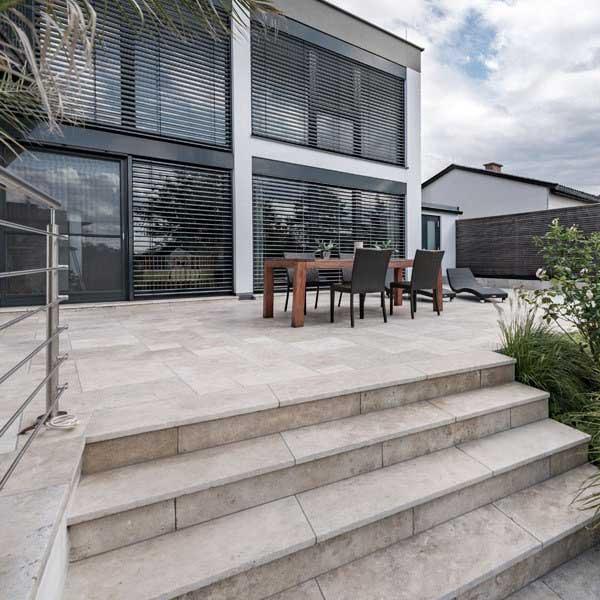 Du travertin clair sur une grande terrasse ouverte avec une table d'extérieur