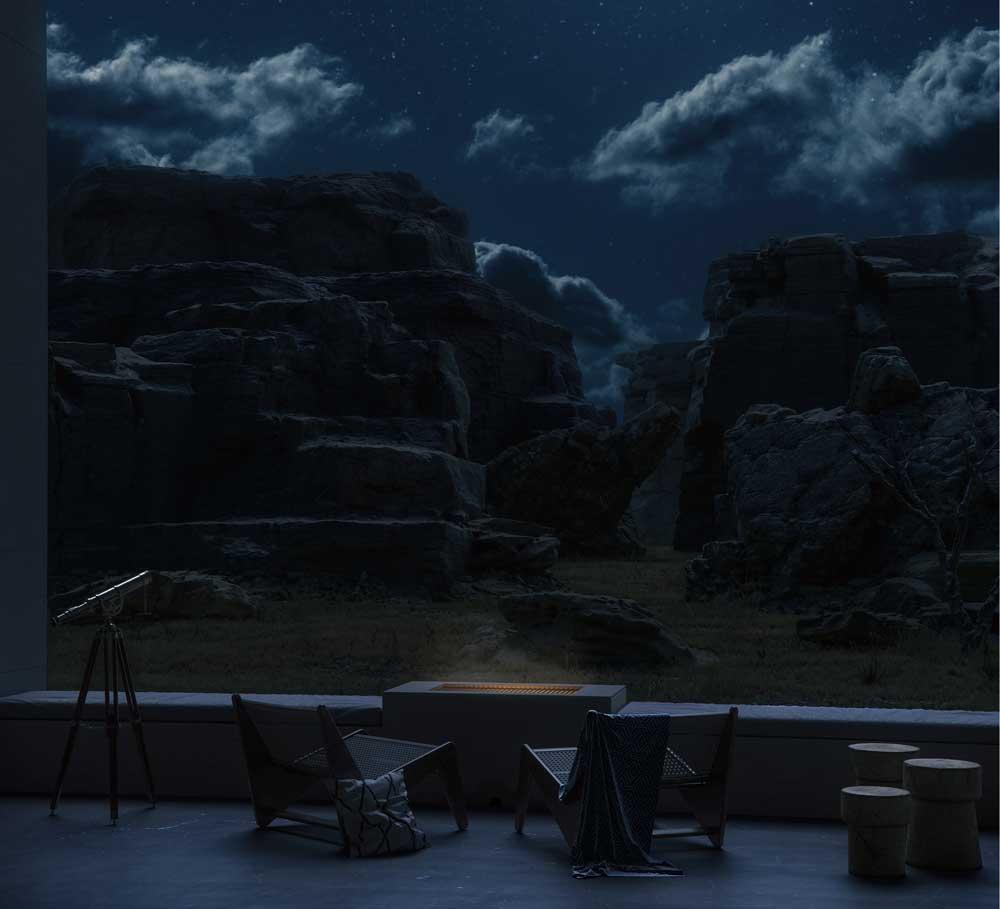 De nuit, le mobilier de jardin offre un coin reposant avec de la petite déco et des fauteuils en bois et cannage