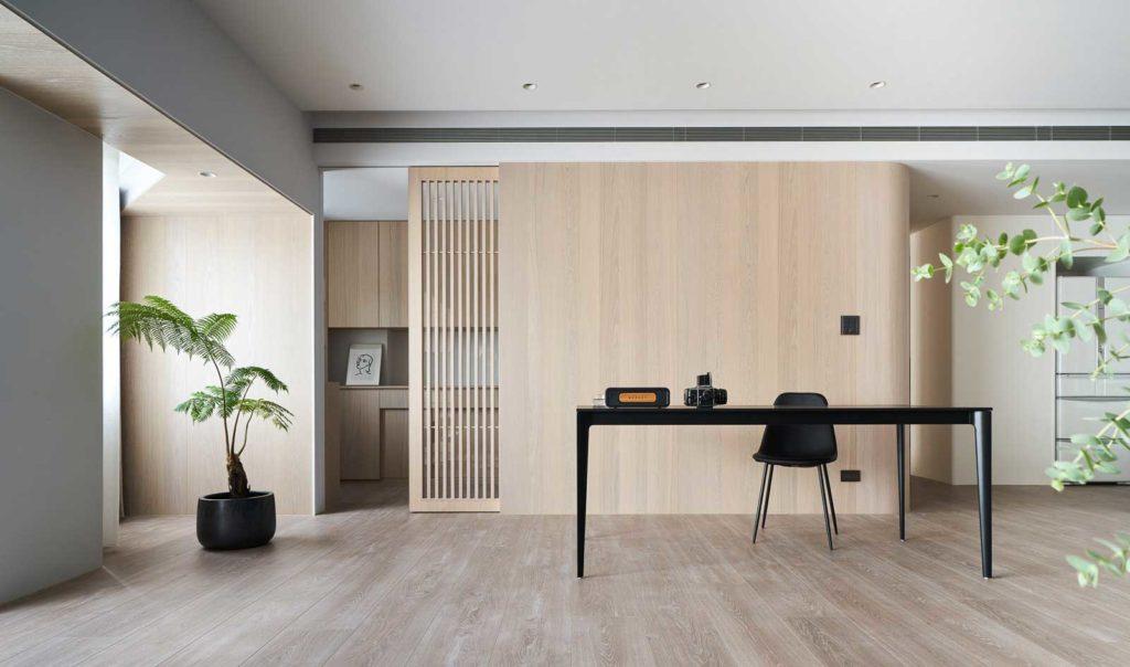 Un grand bureau paré de bois blond et lumineux avec quelques plantes d'intérieur