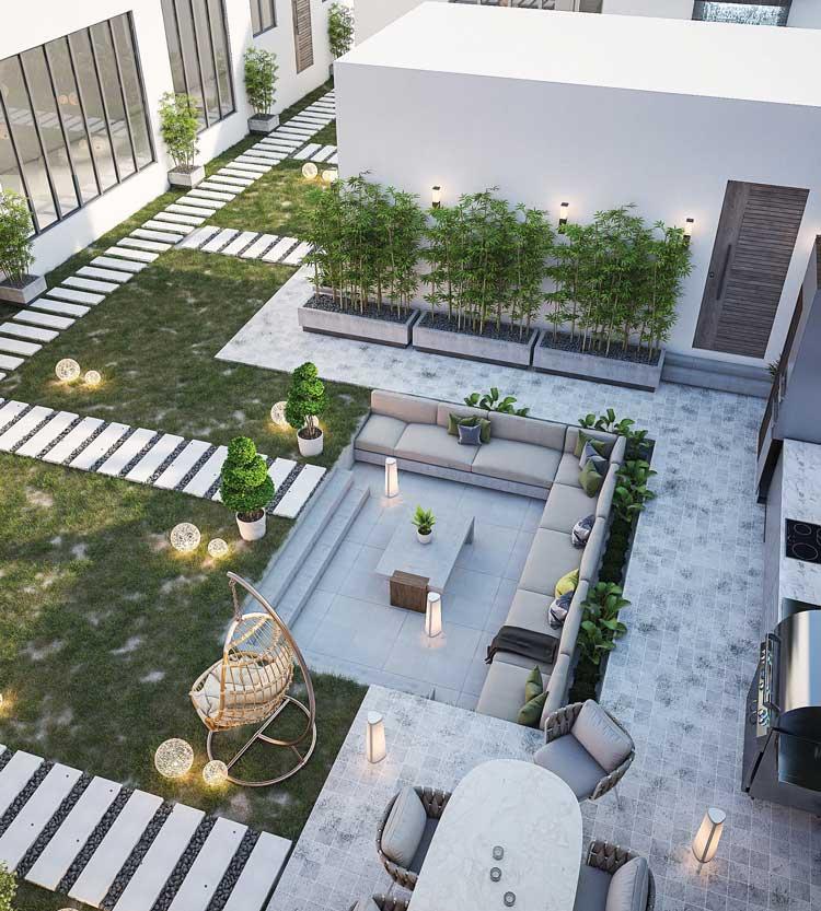 Un grand jardin doté de plusieurs espaces avec salon outdoor, salle à manger et cuisine extérieure décoré d'allées en pas japonais