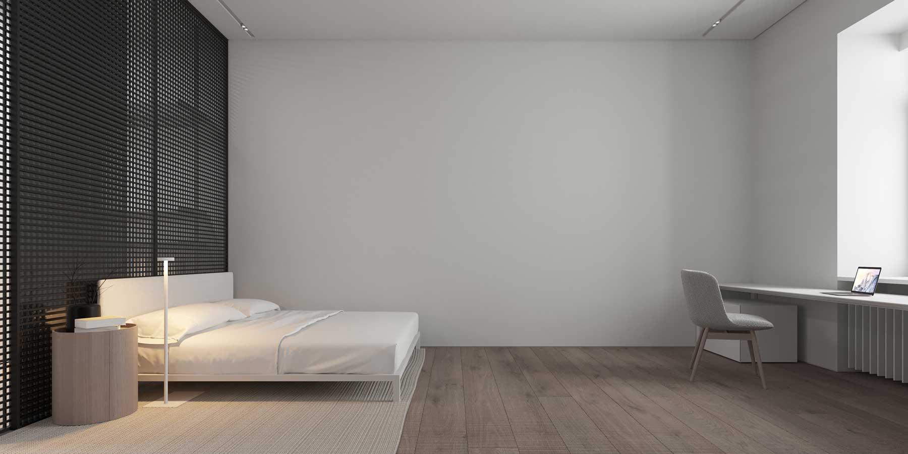 Une grande chambre minimaliste uniquement dotée d'un lit, d'une table de nuit et d'un bureau, avec des murs gris nus qui agrandissent l'espace