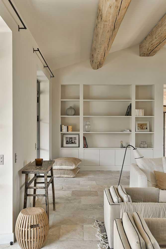 Du travertin en opus romain dans un intérieur lumineux avec des poutres de charpente en bois blond