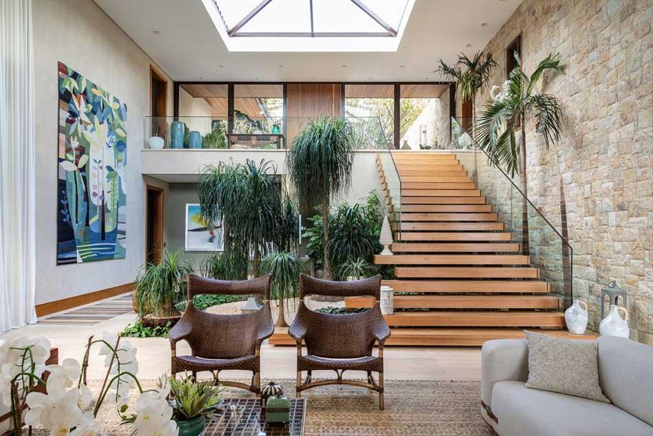 Un jardin végétal en intérieur avec des plantes tropicales qui décorent une grande pièce de vie avec une verrière, un escalier en bois et un mur en pierres
