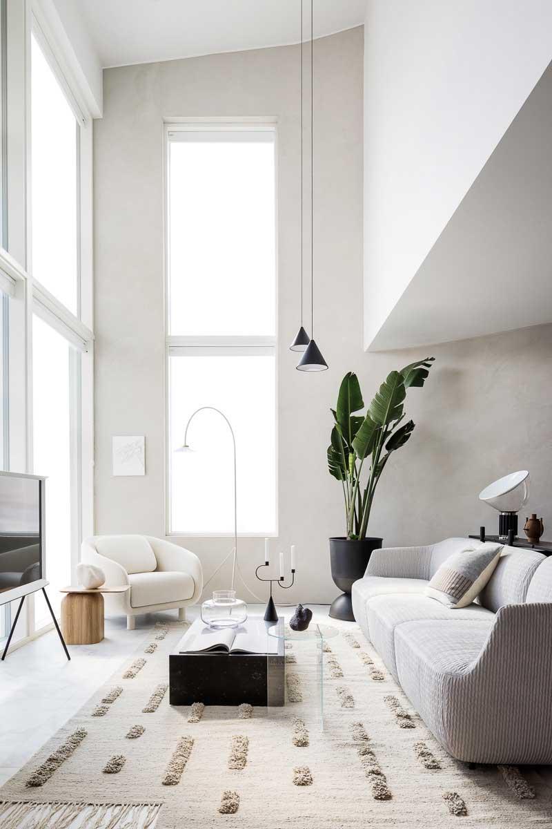 Un arbre d'intérieur colore de vert un coin d'un salon blanc de style total white