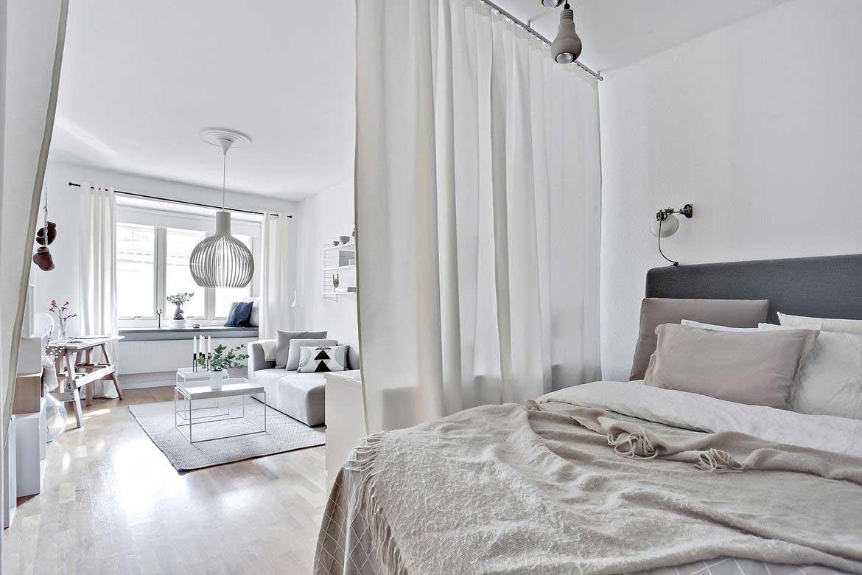 Un grand rideau blanc dans une pièce total white créé un cocon de douceur autour du lit