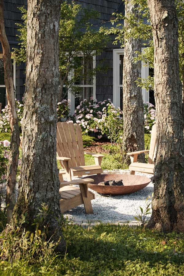 De confortables chaises en bois dans le jardin pour profiter de la nature et du brasero