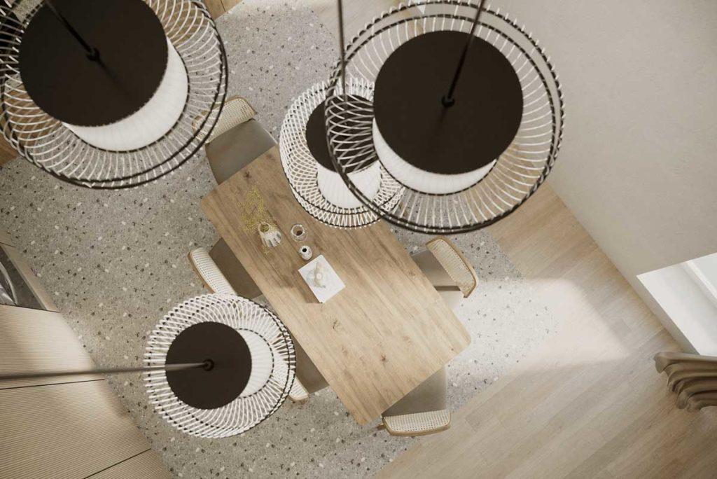 Une salle à manger en terrazzo et bois blond avec des luminaires suspendus en fer noir et blanc