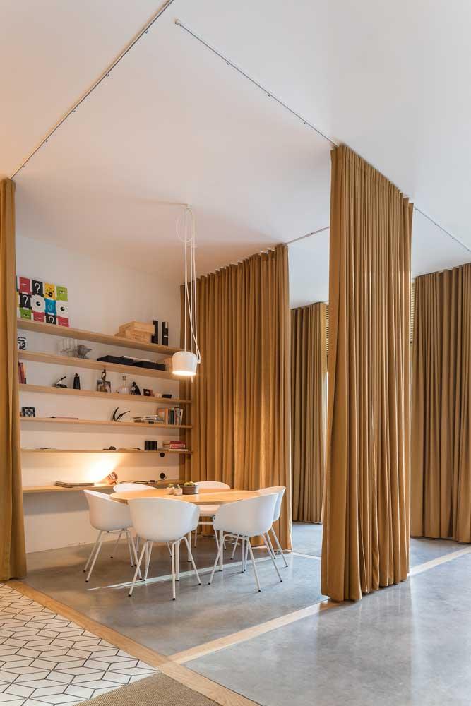 Des rideaux ocre dans la pièce de vie délimite l'espace de la salle à manger