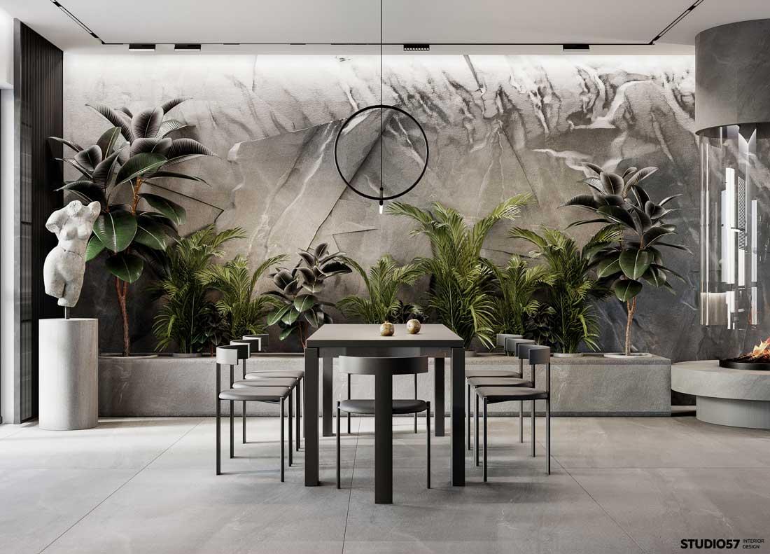 Un alignement d'arbres d'intérieur colore et dynamise une salle à manger monochrome grise avec un mur en pierre naturelle