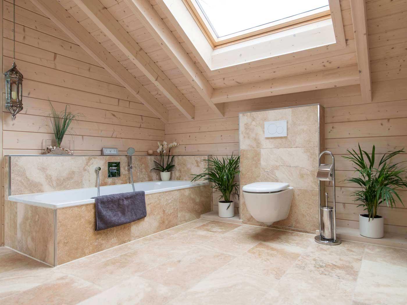 Une salle de bain en travertin sablé et en bois blond avec une baignoire et un velux lumineux