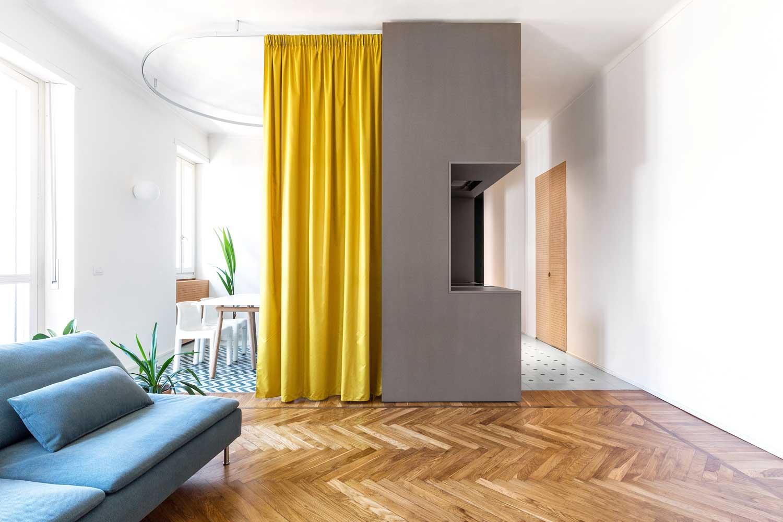Un mur gris et un rideau jaune s'affiche aux couleurs Pantone 2021 pour cerner l'espace central de la pièce
