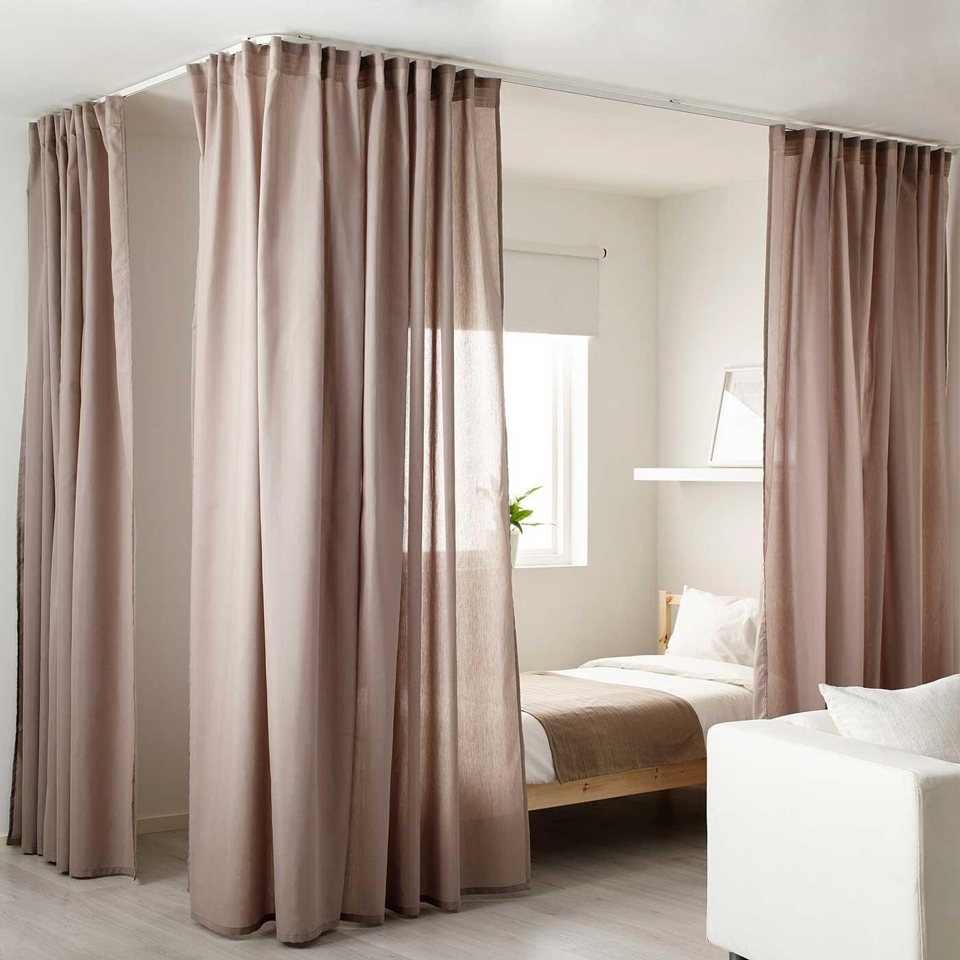 Un lit entouré de grands rideaux pour un espace cocooning de calme et de confort