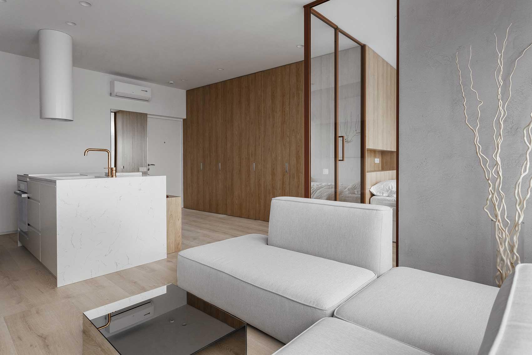 Un studio fonctionnel en blanc et en bois blond avec une verrière qui isole l'espace chambre