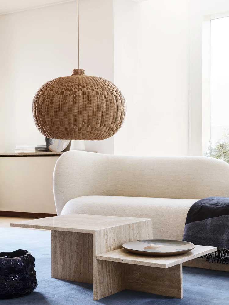 Une table basse géométrique en travertin qui contraste avec les formes arrondies du salon