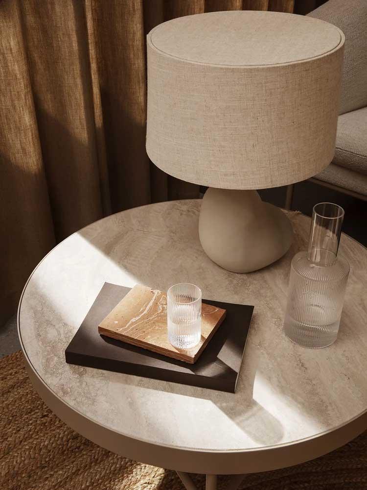 Un revêtement en travertin clair sur le dessus d'une table basse ronde pour une touche de fraîcheur naturelle