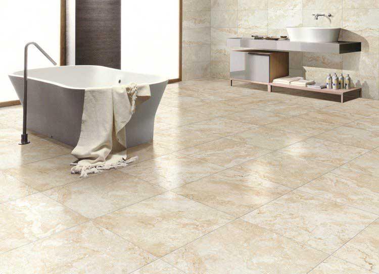 Un carrelage en travertin carré dans une salle de bain spacieuse avec une baignoire grise