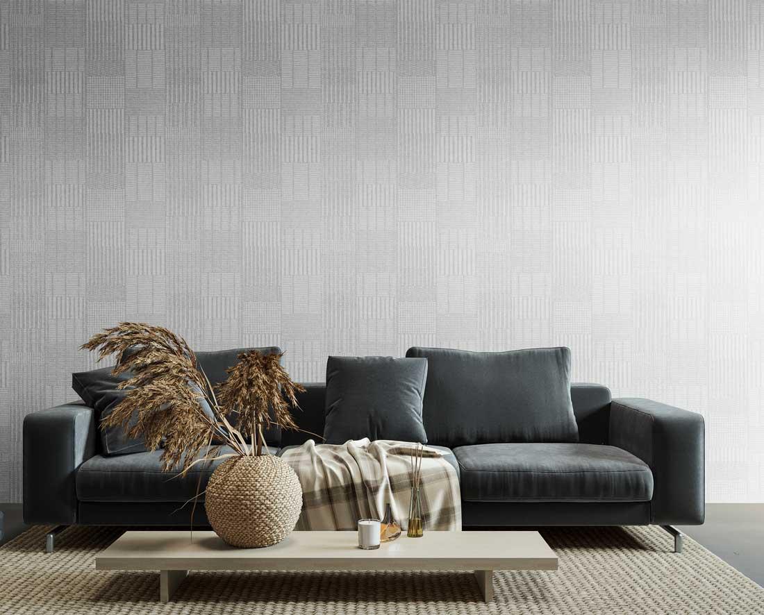Un mur textile géométrique blanc dans un espace salon avec un canapé bleu marine