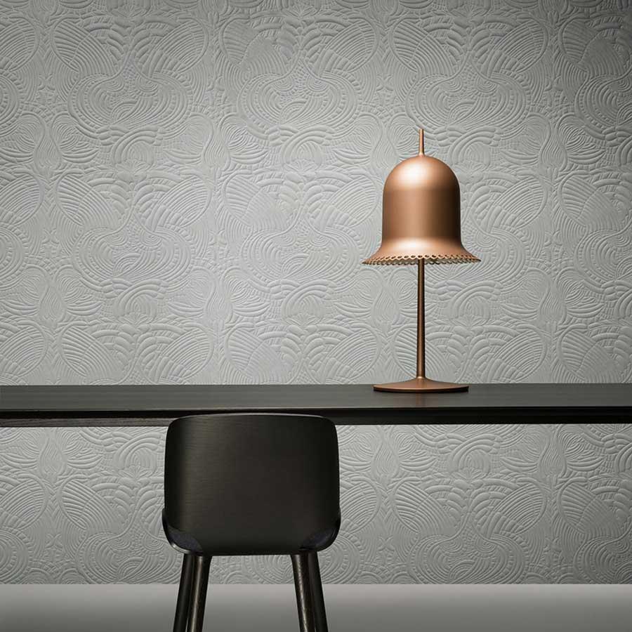 Du mobilier de bureau noir devant un mur textile blanc avec une lampe de bureau rose gold