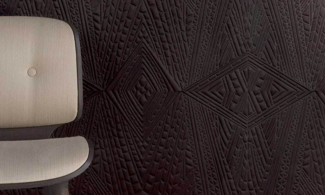 Un revêtement mural en relief noir aux formes géométriques avec un siège au revêtement crème qui contraste