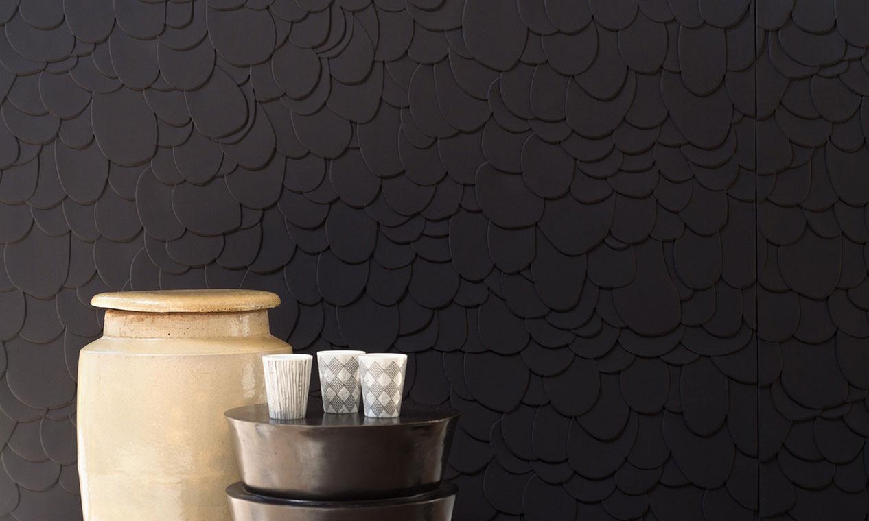 Un revêtement textile mural avec des écailles noires superposées en relief